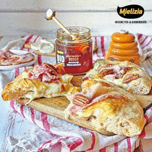 Ricetta facile da fare in casa - Pizza con noci pecan, formaggio caprino, prosciutto arrosto e miele di bosco